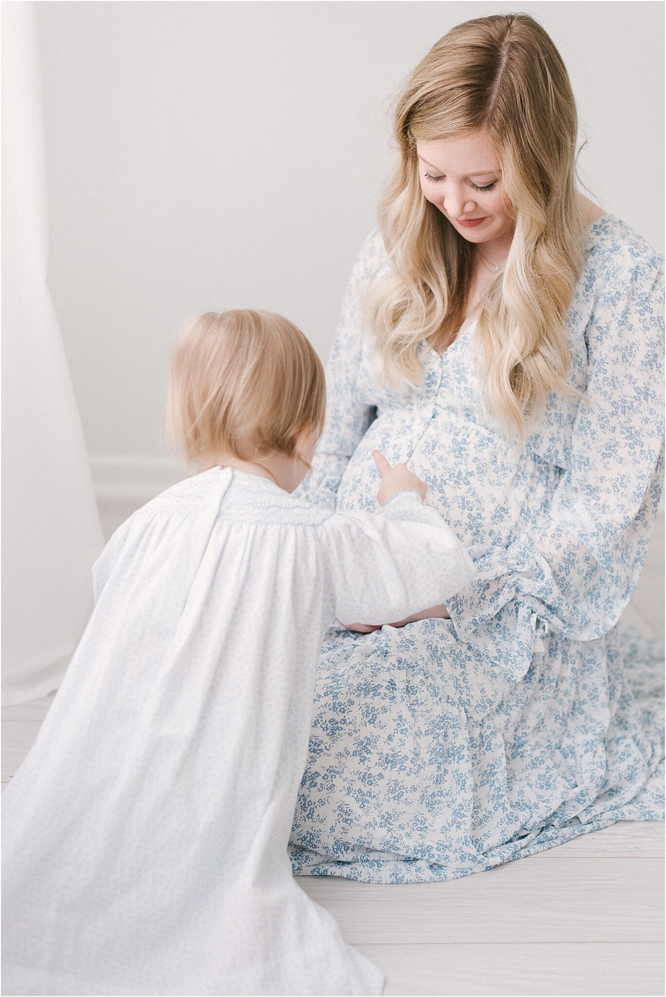 Big sister touching Mom's belly during maternity session with Lindsay Konopa Photography.