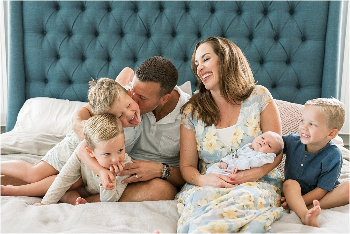 Family laughing together on the bed during Carmel Indiana Lifestyle Newborn Session with Lindsay Konopa Photography.