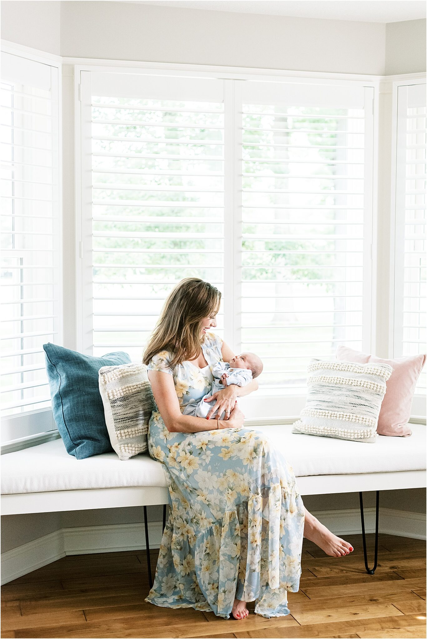 Mom sitting with newborn son in bay window in master bedroom in beautiful Carmel, Indiana home. Photo by Lindsay Konopa Photography.