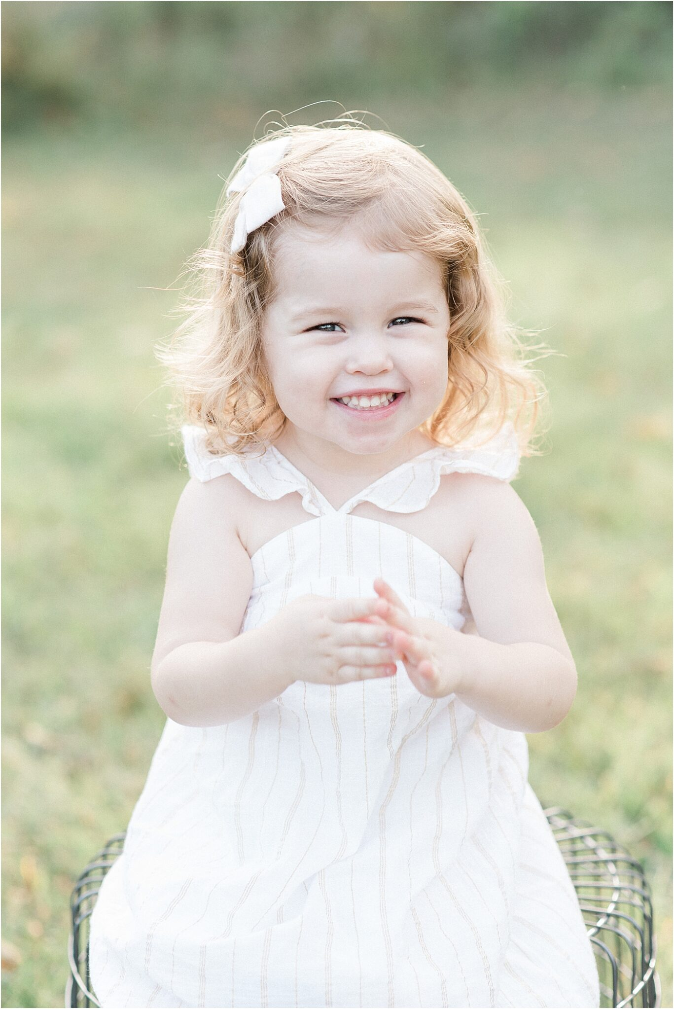 Little girl wearing a white dress and bow and smiling for family photos with Lindsay Konopa Photography.
