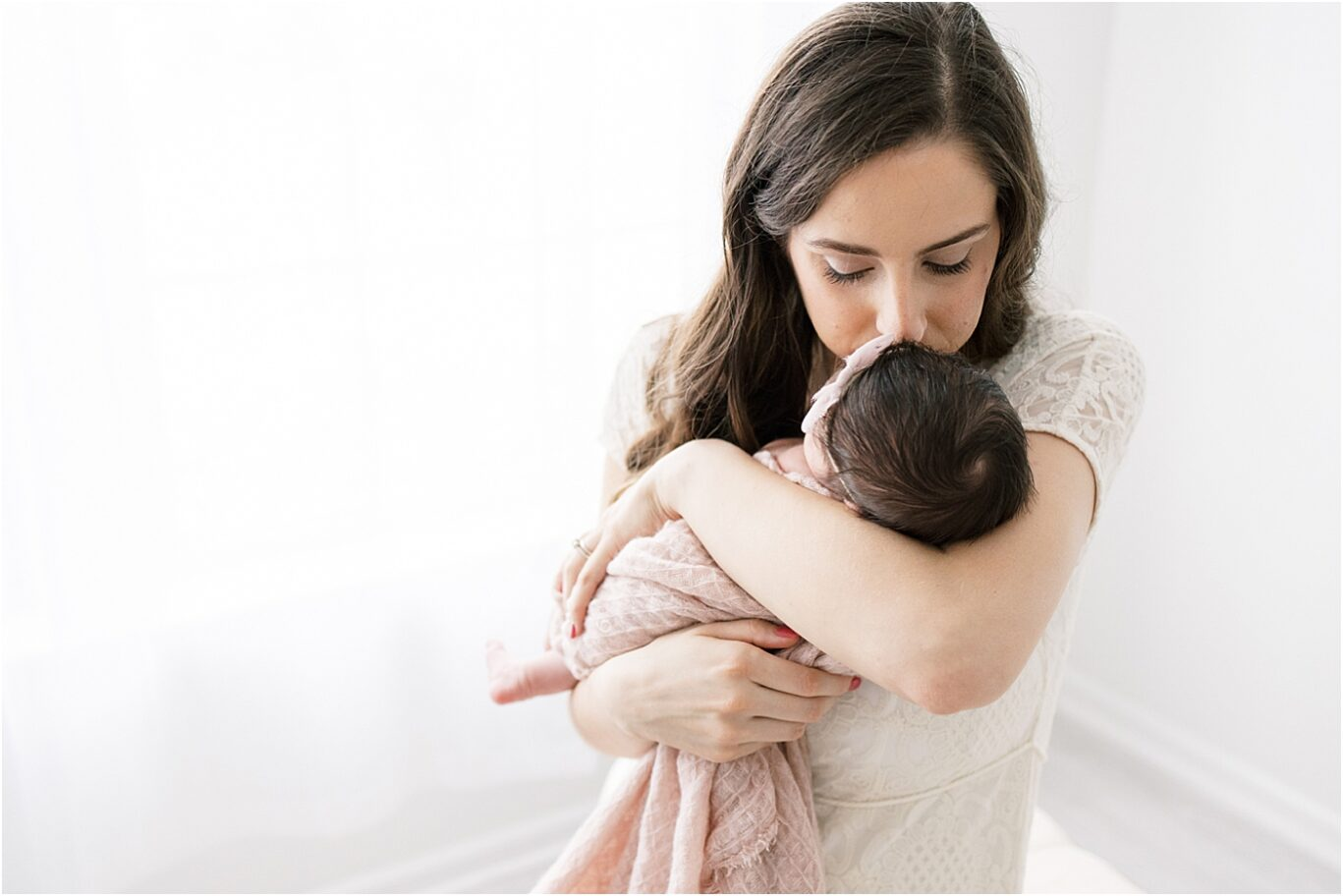 Sweet moment of Mom kissing her baby girl. Photo by Lindsay Konopa Photography.