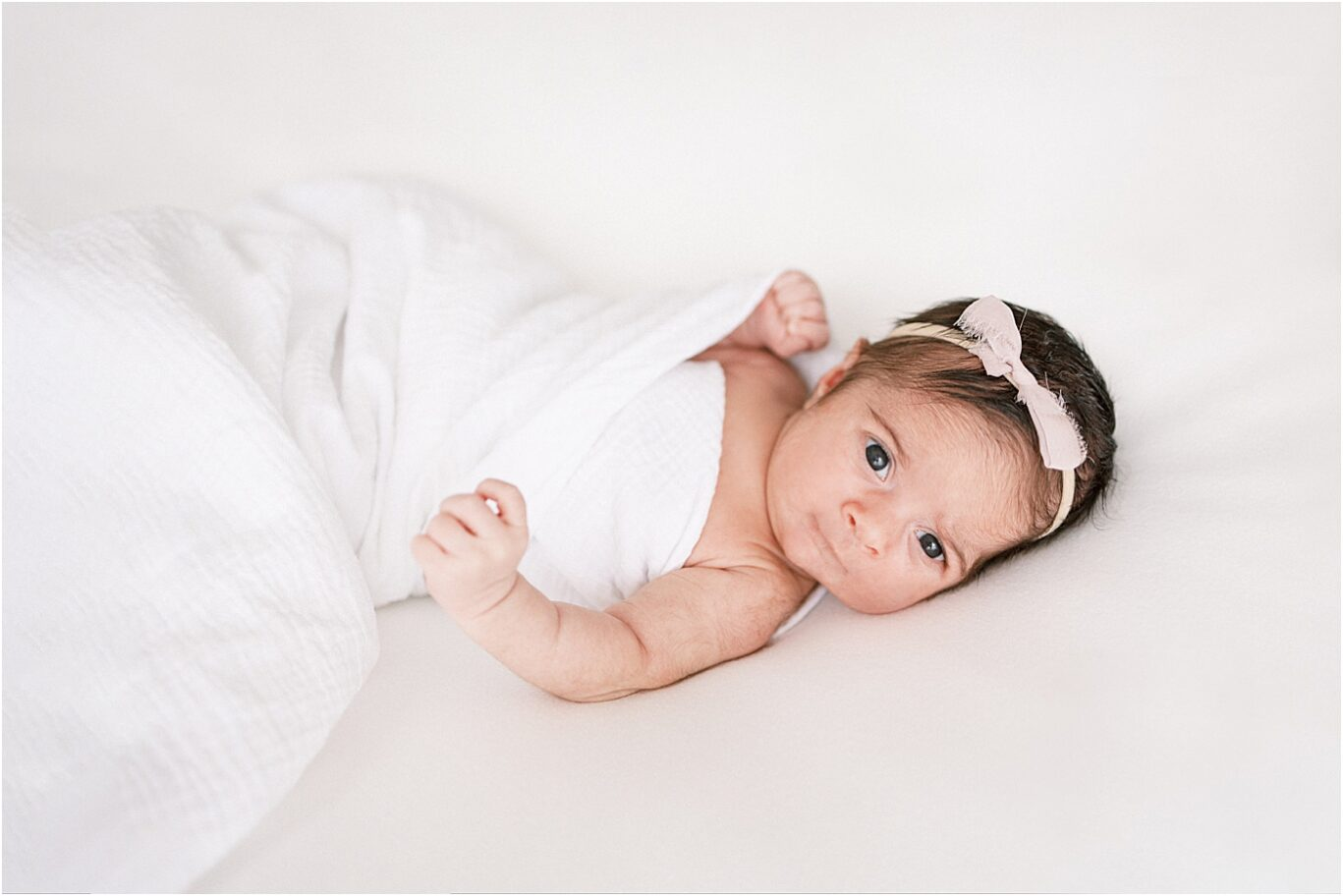 Newborn baby girl swaddled on a white blanket for newborn photos with Noblesville Indiana Newborn Photographer, Lindsay Konopa Photography.