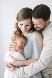 Mom and Dad snuggling their new baby boy.Photo by Lindsay Konopa Photography.