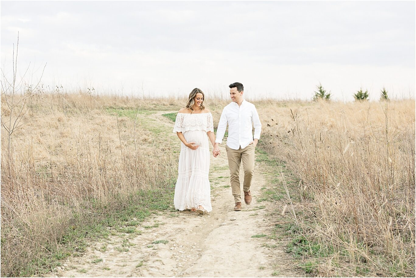 Parents to be walking through a field for maternity session with Lindsay Konopa Photography in Broad Ripple IN.