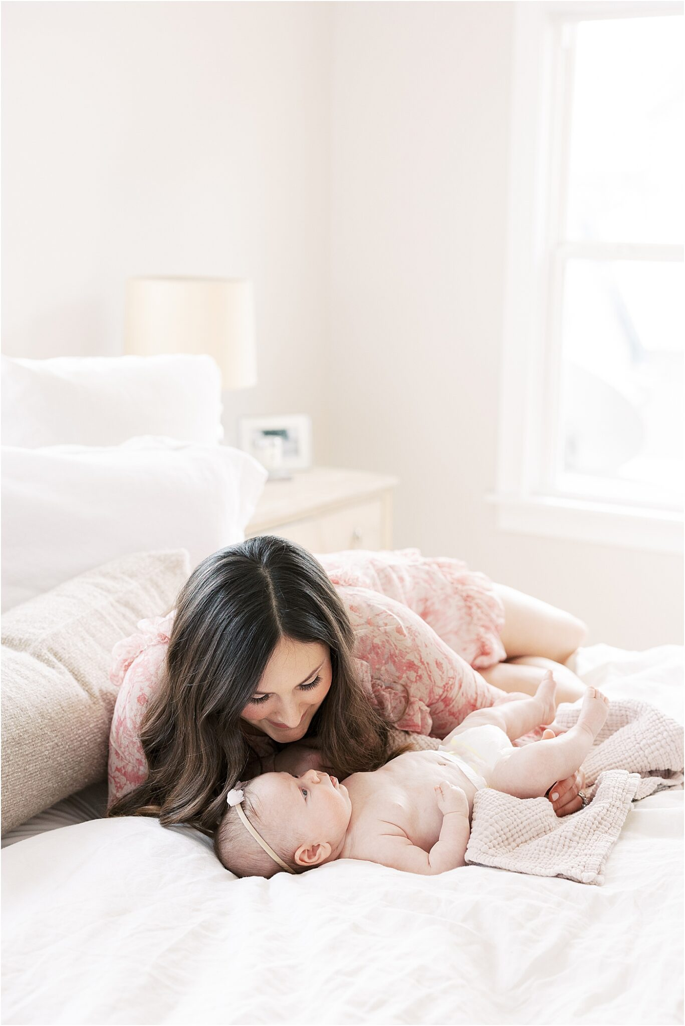 Baby girl laying awake on bed while Mom looks over her. Photo by Lindsay Konopa Photography.