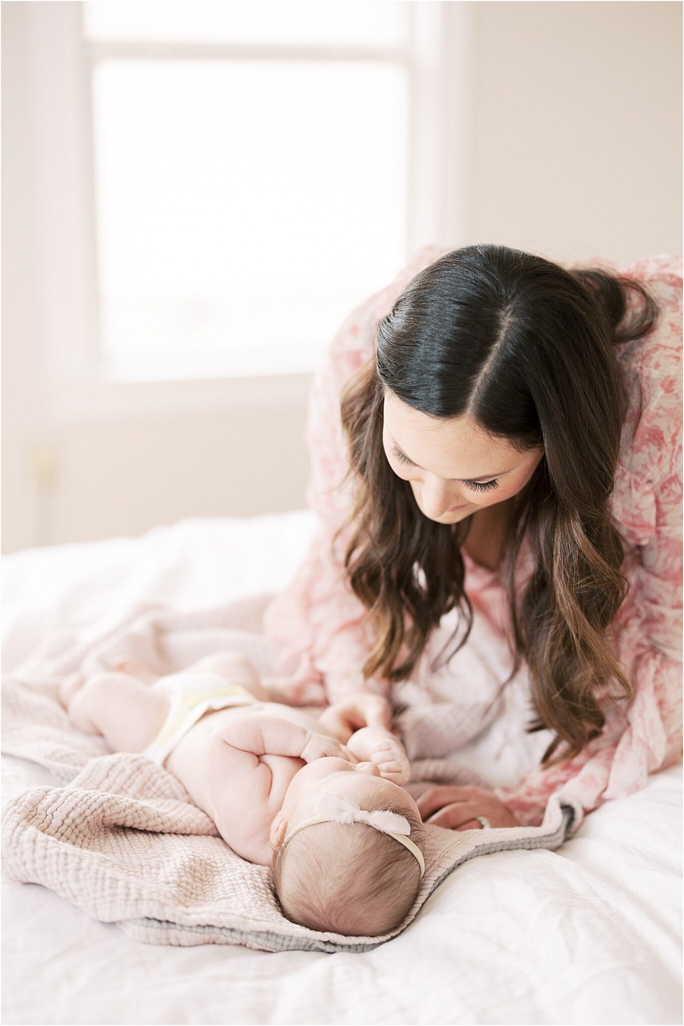 Mom looking at baby girl laying on bed during in-home lifestyle newborn session. Photo by Lindsay Konopa Photography.