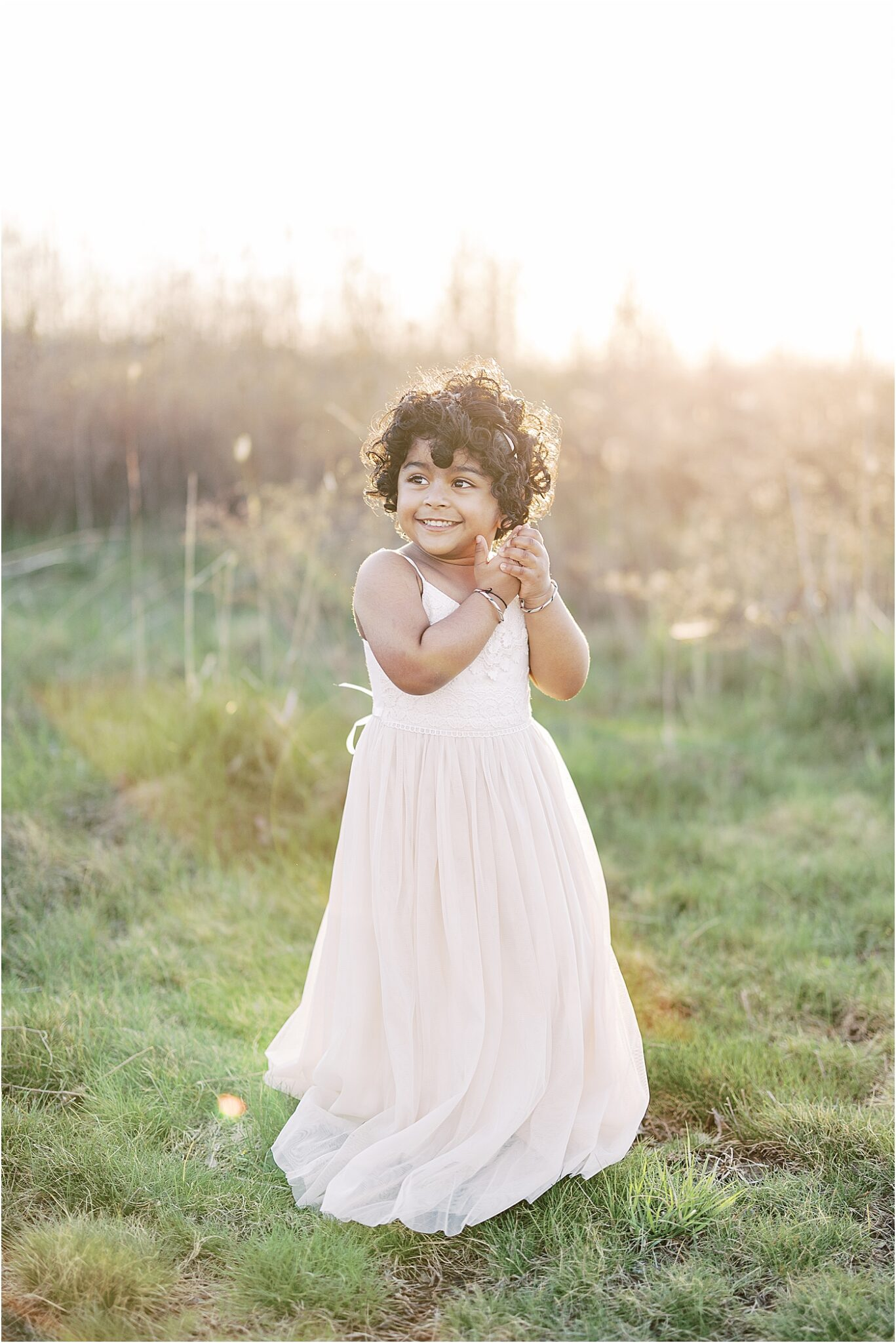 Young toddler girl in a beautiful dress during sunset. Photo by Lindsay Konopa Photography, natural light photographer in Indy.
