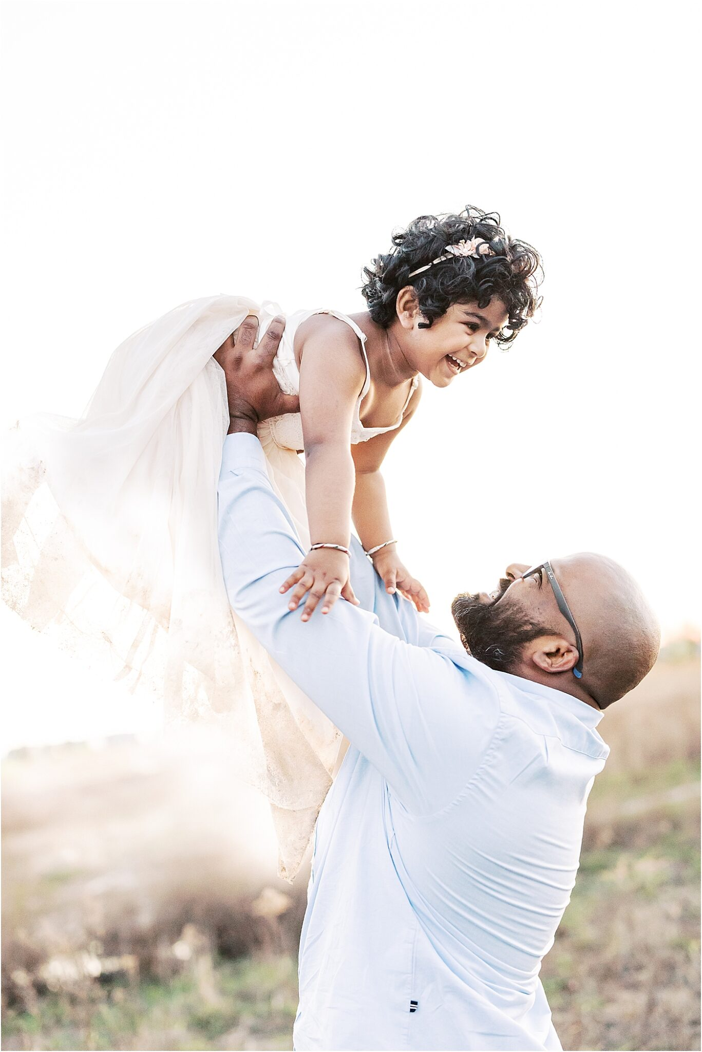 Daddy playing airplane with his daughter during family photoshoot. Photo by Lindsay Konopa Photography.